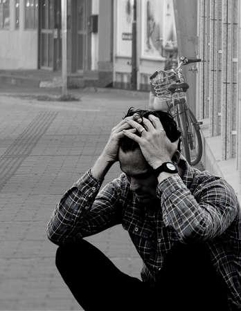 Man sitting on sidewalk looking concerned and depressed