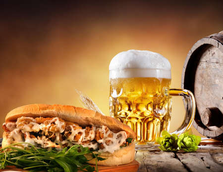 Keg, mug of micro brew beer, and a meatball sub sandwich