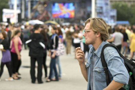 The smoking long-haired guy goes in crowd of people. Shallow depth-of-field. Stock Photo - 7797794