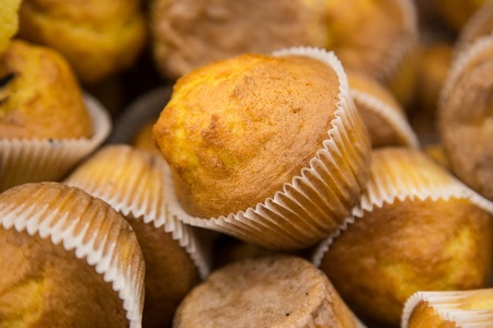 several: Several muffins at the store for sale.