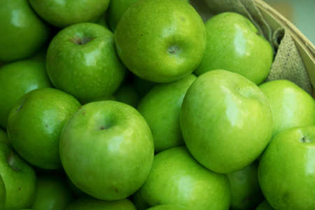 granny smith: Macro photograph of green organic granny smith apples in a bushel basket at farmers market.