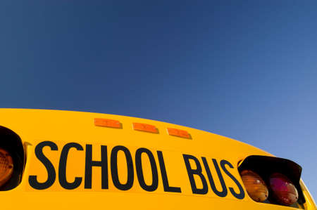 school activities: School bus under a blue sky with copy space.