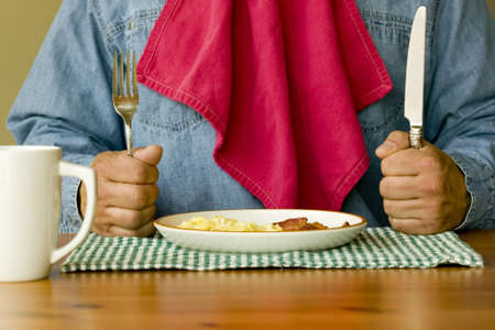Hungry man holding knife and fork with napkin tucked in shirt ready to eat bacon and eggs for breakfast.