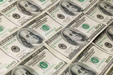 monies: Money background pattern of one hundred dollar bills.