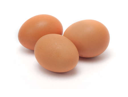 Three yellow chicken eggs on white background Stock Photo