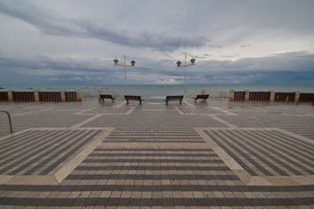 Four benches on the waterfront in rainy weather Stock Photo
