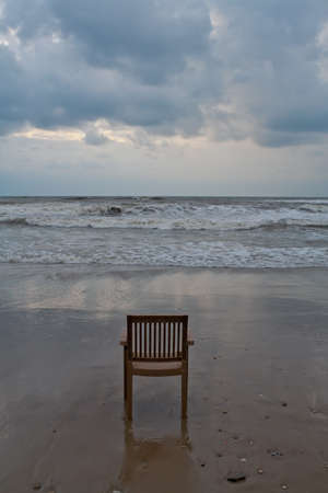 A lonely plastic chair on the beach Stock Photo