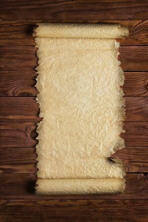 Antico rotolo o papiro su sfondo di legno Archivio Fotografico - 84549628