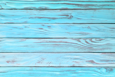 Old wood texture painted in teal or turquoise color. Light blue wooden table, top view
