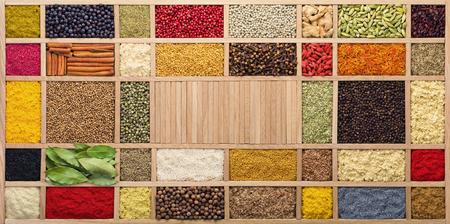 Specerijen en kruiden in houten kist, bovenaanzicht. Kruiden van over de hele wereld voor het koken van voedsel. Stockfoto