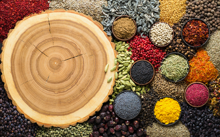 Various spice  scattered on wooden background with empty space for  menu or dish.