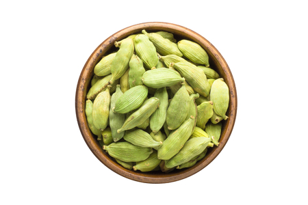 cardamom seeds seasoning in a wooden bowl, top view. spice isolated on white
