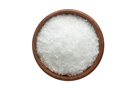 Coconut powder seasoning in a wooden bowl, top view. spice isolated on white