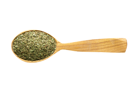 dried mint for adding to food. spice in wooden spoon isolated on white. seasoning of delicious meal.
