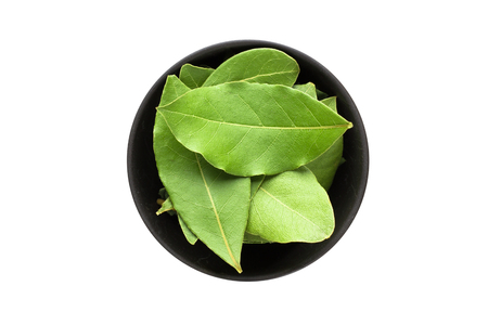 dried bay leaves in bowl, top view, isolated on a white background. organic spice Banco de Imagens