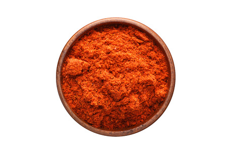 chili powder seasoning in a wooden bowl, top view. spice isolated on white