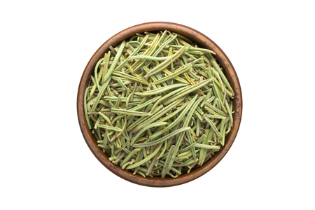 dried rosemary seasoning in a wooden bowl, top view. spice isolated on white Banco de Imagens