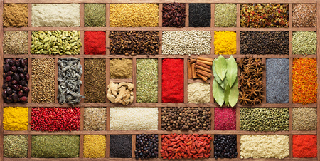 Spices and herbs in  wooden box, top view. Seasonings from all over the world for cooking food.