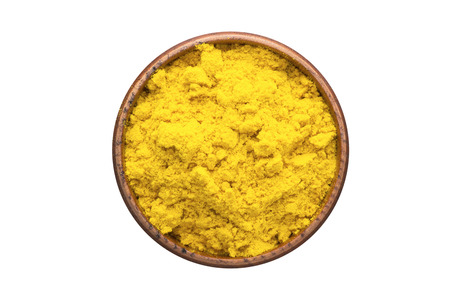 turmeric powder seasoning in a wooden bowl, top view. spice isolated on white Banco de Imagens