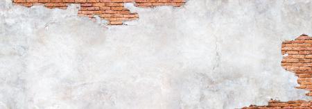 Damaged plaster on brick wall background. Brickwork under crumbling texture concrete surface