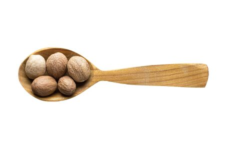 whole nutmeg for adding to food. spice in wooden spoon isolated on white. seasoning of delicious meal. Banco de Imagens