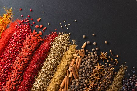Set of flavors on blackboard background, top view. Spices for cooking tasty food.