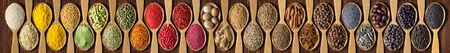 Colorful spices on background wooden table. Seasonings and herbs in wooden spoons for design website headers.
