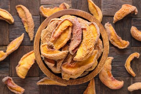dried peaches in bowl on wooden table background.