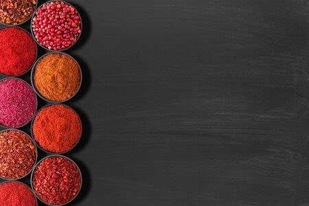 set condiments on table with space for text or recipe. spices for food red shades, on  black chalkboard.