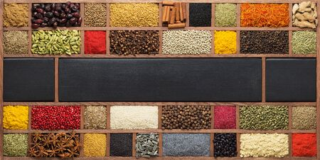 Collection of spices in wooden box, top view. Indian condiments as background for packing with food.