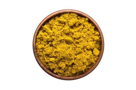 curry powder seasoning in a wooden bowl, top view. spice isolated on white Banco de Imagens