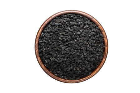 Nigella or Black cumin seeds seasoning in a wooden bowl, top view. spice isolated on white Banco de Imagens