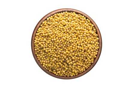 mustard seeds seasoning in a wooden bowl, top view. spice isolated on white Banco de Imagens