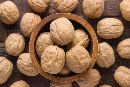 shelled walnut in bowl on wooden table background. Banco de Imagens