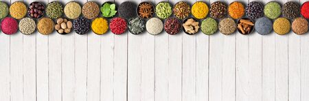 Spices on white table background. Colorful condiments and herbs for Indian food