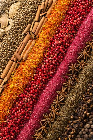 Various spices and herbs are scattered on table. Seasoning background for packaging with food.