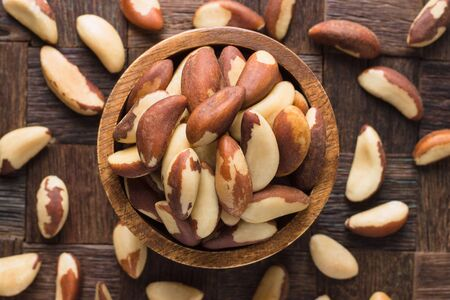 brazilian nuts peeled in bowl on wooden table background.