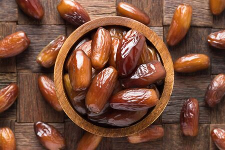dried date fruit in bowl on wooden table background. Banco de Imagens