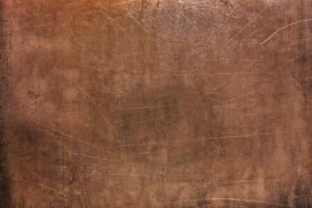 Pomarańczowa metalowa powierzchnia, brązowe lub miedziane tło