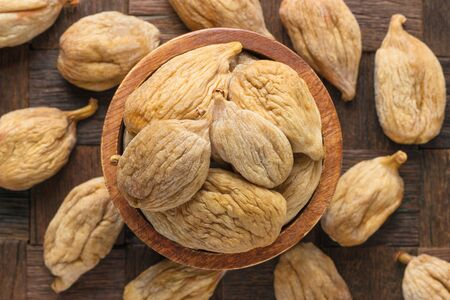 large dried figs in bowl on wooden table background.