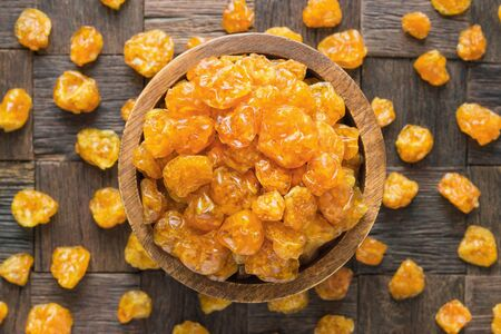 candied fruit, dried physalis with sugar in bowl on wooden table background.
