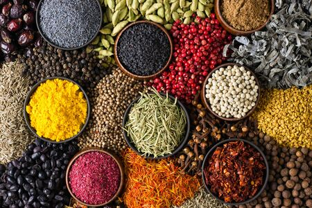 Spices and herbs background. Different seasonings are scattered in color.