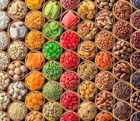 assorted nuts and dried fruit background. organic food in wooden bowls, top view.