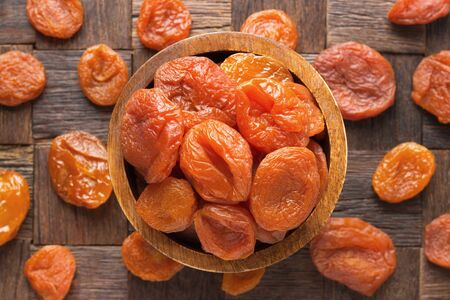 natural dried apricots in bowl on wooden table background. 免版税图像