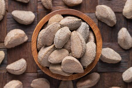 shelled bertholletia, brazil nuts in bowl on wooden table background. 免版税图像