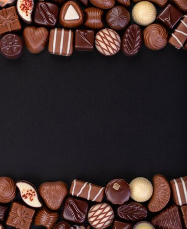 chocolate candy on black table with copy space, sweet food background.