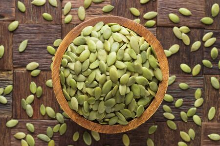pumpkin seeds peeled in bowl on wooden table background. 免版税图像