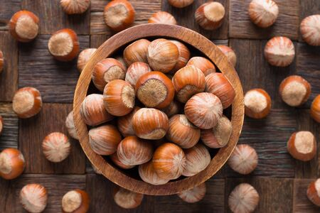 shelled hazelnut in bowl on wooden table background.