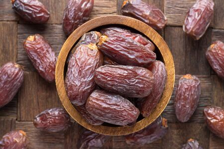 dried royal dates fruit in bowl on wooden table background.