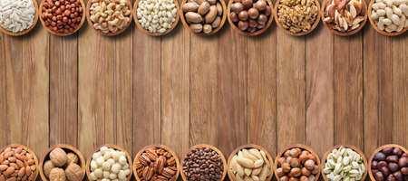 collection nuts and seeds on wooden table background with empty space.